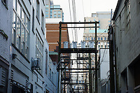Overhanging electrical wires and wooden poles in a back alley, Vancouver, BC, Canada