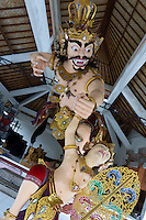Ogoh -Ogoh (demon)  sculpture of Kala Tumbang Wayang, abducting a child, Central Bali. Balinese New Year called Nyepi (around march according to lunar calendar),  is a silent day of meditation and spiritual purification. One day before exorcist rituals are held for purification and balance of polar powers of the universe, first at noon by a priest (exorcism called Caru or Tawur Agung) and later on after sunset in a popular, carneval-like procession of Ogoh-Ogoh, symbolizing bhuta kali (demon, bad spirits,bad habits),  so all the bad spirits leave the village and the island.  Loud, rhythmic music and special performances are part of the procession called Ngerupuk. Road crossings are major spots of exorcism and special ogoh-ogoh performance, since demons often like to dwell here. At Nyepi, the following day, there is 24 hours silence, no vehicle or people on the street, no light or fire, no working  all the bad spirits should think, the island is abandoned and leave the island. Day after Nyepi is a day of reconciliation  new year starts purified.