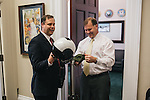 Congressman Jim Bridenstine is given his old flight gear by his former squadron mate Ben Sale, right, before heading to the Capitol for a vote on Sept. 19, 2013.