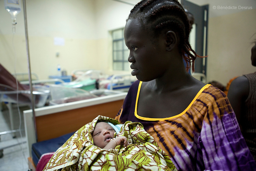 """July 6, 2011 - Juba, Republic of South Sudan - Agnes Gago, a South Sudanese pregnant woman, after giving birth to her second child at the Juba Teaching Hospital, South Sudan's oldest, and by far the largest and best-equipped in the new country. She said, """"I'm not scared but I came to the hospital because I needed help. I can't give birth at home because I'm unable to cut the cord and clean the baby myself. At home there are no facilities and no medications"""". South Sudan has the highest maternal mortality rate in the world. One in seven South Sudanese women is likely to die because of complications from delivery. Just 10 per cent of South Sudanese women have access to medical professionals during childbirth. Photo credit: Benedicte Desrus"""