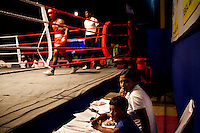 Saihaan, Razia's son, spends a few minutes next to Razia Shabnam while she judges a bout at an all-India invitational boxing competition in the neighbouring town of Burnpur, Calcutta, West Bengal, India. Razia Shabnam, 28, was one of the first women boxers in Kolkata. She was also the first woman in her community to go to college. She is now a coach and one of only three international female boxing referees in India. Photo by Suzanne Lee for Panos London