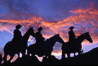 Dramatic view of cowboys on horseback in silhouette under sunset clouds and sky.