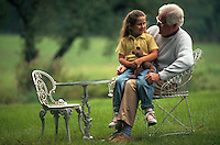 Granddaughter sitting on grandfather's lap outside.