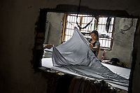 Rural migrants work in a garment sweatshop on the outskirts of the southwestern Chinese megapolis of Chongqing. They often work through the nights, earning 1,000 - 6,000 yuan per month depending on work load, a decent income compared with subsistence farming. For many, this is a long and arduous step in the transition from farming to urban living. China is hoping by relocating farmers into cities they would start to buy food, making a break from the cycle of farmers consuming only what they produce.The Chinese government plans to move 250 million rural residents into urban areas over the coming dozen years though it is unclear whether people want to move and where the money for this project will come from. Further urbanisation is meant to drive up consumption to counterbalance an export orientated economy and end subsistence farming but the drive to get people off the land is causing tens of thousands of protests each year. /Felix Features
