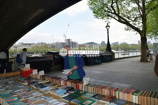 Second hand book stall on South Bank, London UK April 2019. Posed by model
