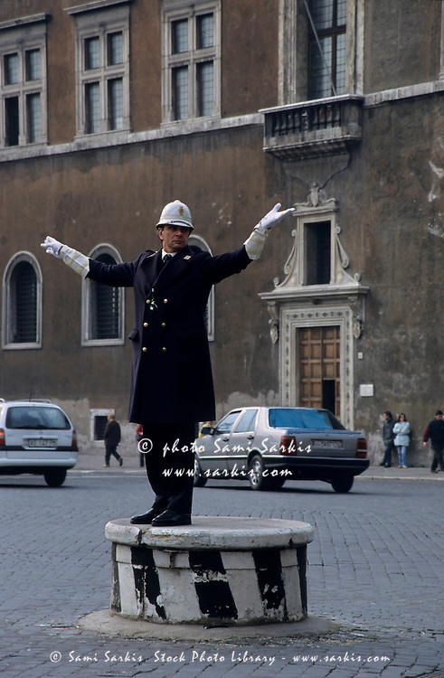 Police officer directing traffic in the Piazza Venezia, Rome, Italy.