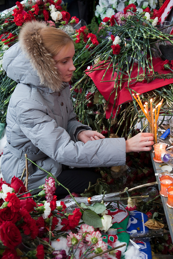 Moscow, Russia, 15/01/2011..A woman lights candles during a rally at the bus stop where Spartak soccer fan Yegor Sviridov was killed in a street fight with a group of men from the southern Caucasus, leading to a nationalist backlash that has spilled into racist violence on the streets of Moscow and other Russian cities. The rally on the 40th day after Sviridov's death was attended by a mixture of local people, football fans and Russian nationalists.