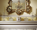 The mirror and mantlepiece in the Drawing Room at Fenton House. On the mantlepiece are examples of c18th Rococo glassware. A chandelier can be seen through the mirror.
