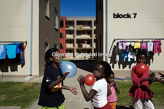 SOWETO, SOUTH AFRICA MAY 4: Children play outside the apartment block where they live on May 4, 2013 in Jabulani, section of Soweto, South Africa. Jabulani flats is one of the first apartment building developments in Soweto and local residents are just beginning learn how to live in an apartment. The residents of Soweto has seen massive investment such as shopping malls, parks, outdoor gyms in the township. Soweto today is a mix of old housing and newly constructed townhouses. The population in Soweto is estimated to be around one million people. A new hungry black middle-class is growing steadily. Many residents work in Johannesburg but the last years many shopping malls have been built, and people are starting to spend their money in Soweto (Photo by: Per-Anders Pettersson)
