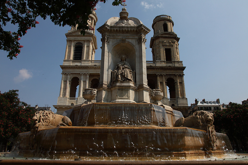 Paris Left Bank: The fountain of place Saint Sulpice with water, the church on the background and a green tree branch, in a sunny spring day.<br />