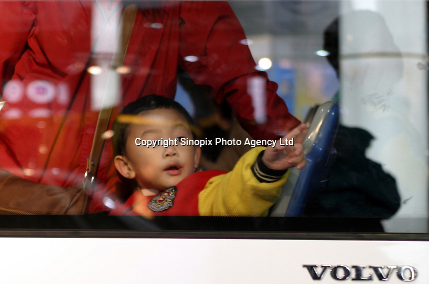 A child takes a seat in a Volvo bus on display at the 2003 Shanghai International Industry Fair in Shanghai, China. Sponsored partly by the government, the fair hopes to show the growing technological sophistication of its industries..