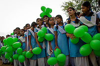 Indian school girls awaits the arrival of the Queens baton relay on the outskirts of the central Indian state of Chhattisgarh on the 13th of August 2010.