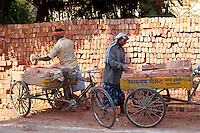Indian men stacking TATA bricks in the city of Varanasi, Benares, Northern India