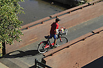 Boy riding his bike on a sidewalk in Denver, Colorado. .  John offers private photo tours in Denver, Boulder and throughout Colorado. Year-round.