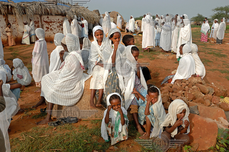 Worshippers in white robes pray outside St Mary's church in the village of Fithi ('justice'). .