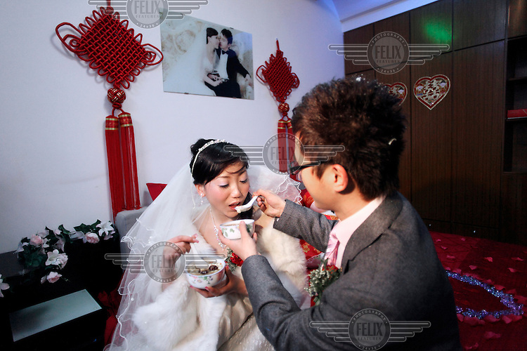 A bride and groom feed each other from bowls of soup, a version one of the many rituals that surround a Chinese wedding.