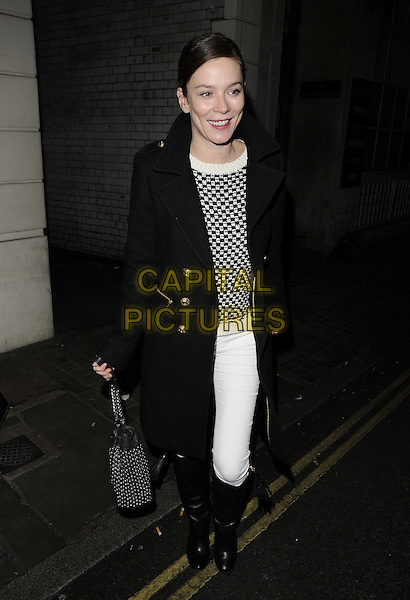 Anna Friel.departed after the evening performance of 'Uncle Vanya', Vaudeville Theatre, The Strand, London, England, UK, .15th December 2012..full length black coat knee high boots  white jeans trousers jumper bag smiling .CAP/CAN.©Can Nguyen/Capital Pictures.