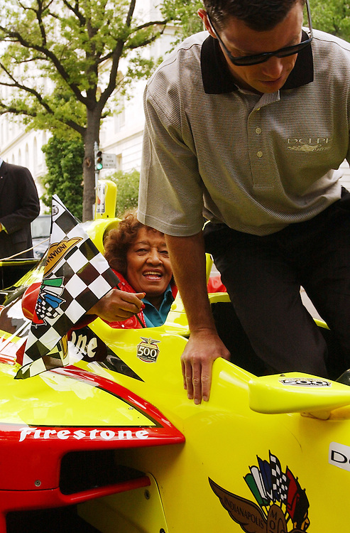 Rep. Julia Carson, D-Ind., gets ready for a ride in an Indy race car driven by current driver Scott Sharp, Wednesday, near Cannon.  Drivers and other members of the Indy racing profession were on hand to celebrate Indiana Day.  The car is made for  passengers and equipped with a motorcycle engine