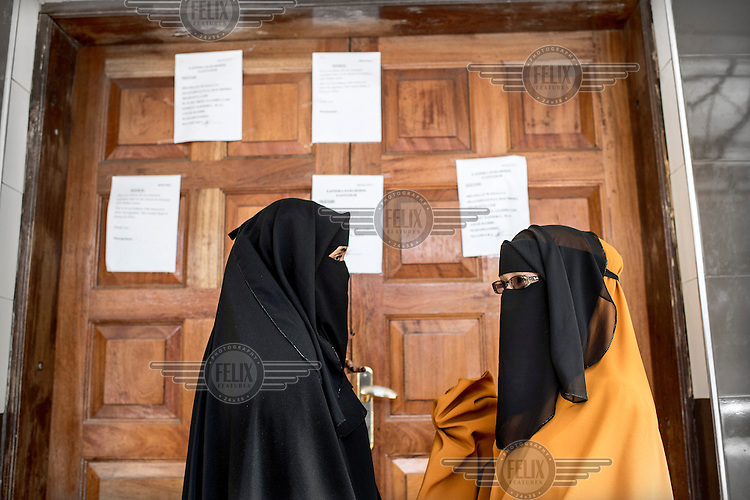 Two veiled women stand in front of the closed doors of a Dahabshiil office in Eastleigh. On the doors apology letters about the sudden closure of the remittance office. Many people in Eastleigh depend on money send via Dahabshiil from relatives in the diaspora but the Kenyan authorities have accused the bank of being a conduit supplying funds to Al-Shabaab and forced it to suspend operations in Kenya from April to June 2015.