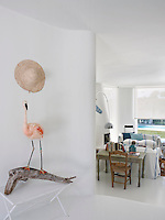 A quirky sculpture of a flamingo with a quizzical expression on a large piece of driftwood stands in the entrance hall