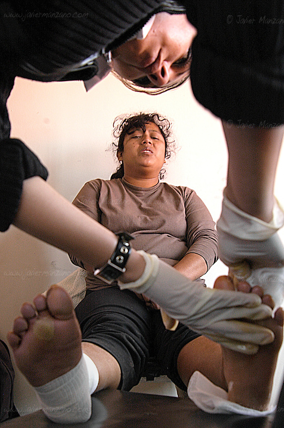 A twenty four year old woman from the state of Chiapas, Mexico, sits on a chair in the offices of ?Grupo Beta? (an immigration aid organization in Nogales Mexico), after falling several feet into a canyon while crossing the border with her twelve year old son and husband. She could hardly walk when found by the Border Patrol stranded in the middle of the desert.