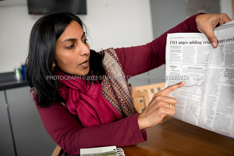 3/13/2014&mdash;Seattle, WA, USA<br /> <br /> Seattle city council member Kshama Sawant speaking at City Hall. Seattle is debating whether or not to raise the city&rsquo;s minimum wage to $15. The recently elected council member, Sawant is a member of the Socialist Alternative Party. She has moved from her role as an activist in the fight for higher wages to working for a citywide $15 minimum wage inside City Hall Seattle. <br /> <br /> Here Sawant points to a Seattle Times article on the effects of the minimum wage increase in San Fransisco a decade ago and how it had no impact on jobs.<br /> <br /> Photograph by Stuart Isett<br /> &copy;2014 Stuart Isett. All rights reserved.