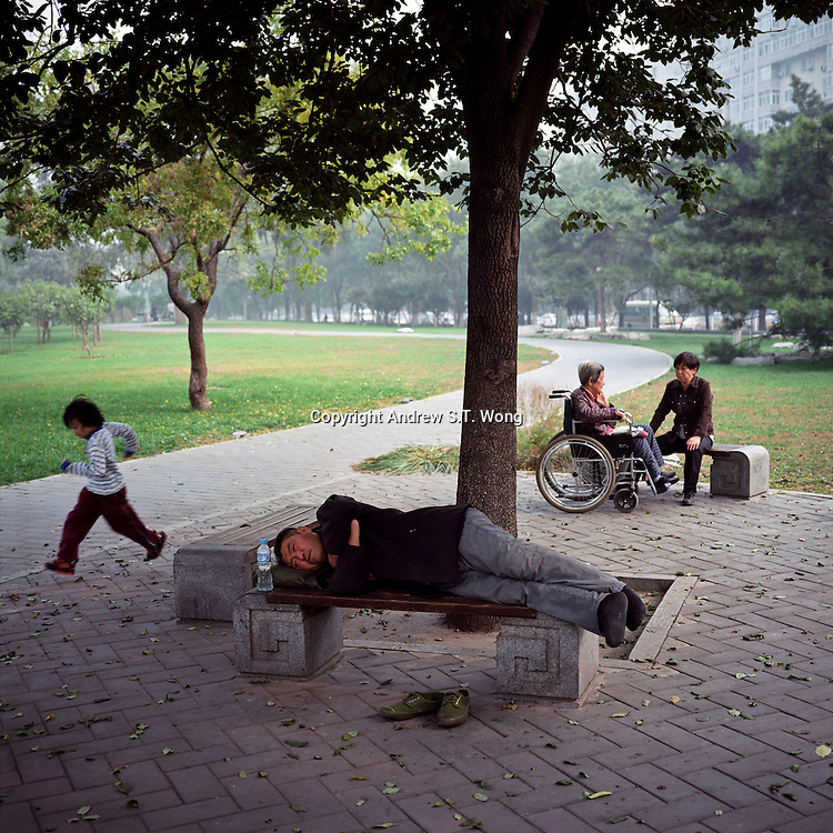 A Chinese man takes an afternoon nap as a child runs past at a park in Beijing, October 2011. (Mamiya 6, 75mm f3.5, Kodak Ektar 100 film)