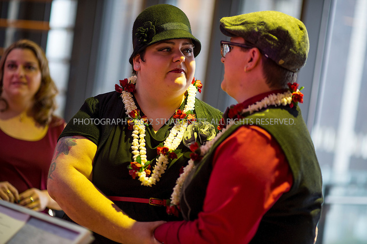12/9/2012--Seattle, WA, USA..Diane, left, and  Amanda Ruff, right, of Tacoma, get married Seattle City Hall. They have been together for 10 years....On the first day same sex couples were allowed to marry in Washington State, Hundreds of well-wishers braved cold and rain to celebrate 133 weddings at Seattle City Hall. Washington, Maine and Maryland last month became the first U.S. states to extend marriage rights to same-sex couples by a popular vote, in a leap forward for gay rights. A crowd of several hundred people waited outside City Hall in the cold to cheer couples as they descended the steps, some throwing bird seed, rice, blowing bubbles and handing flowers to the newlyweds...©Stuart Isett. All rights reserved.