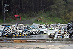 """Minamisanriku, Miyagi, Japan - Many crushed cars are collected and one gateway to a Shinto shrine is fallen dawn in Minamisanriku, one year after the tsunami. The Latin group of volunteers """"Todos con Japon"""" visits Miyagi area during this Golden Week."""