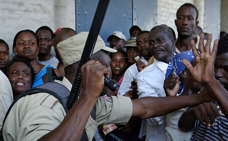 Earthquake aftermath in Haiti on January 21, 2010..A Haitian police officer attempts to control a crowd in front of Soge Bank in Saint Marc, Haiti. Many of these people traveled from Port-Au-Prince and waited since Wednesday night to receive Western Union money transfers..