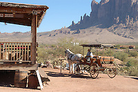 "Goldfield Ghost Town in Goldfield, Arizona is located 40 miles southeast of Phoenix -at the base of the Superstition Mountains- and it has been called ""Gateway to the Superstition Mountains."" Thanks to the discovery of gold in 1892, the town turned into a booming community with a population of four to five thousand people. Facilities included a hotel, a general store, three saloons, boarding houses, a blacksmith, a school house, a hotel, a meat market and a brewery. The mining district had at one point 50 gold mines. While Goldfield's growth and wealth was promising, a decrease in the gold deposits caused Goldfield to decline. Further attempts to bring back Goldfield to its thriving days between 1910 and 1926 failed. Today, Goldfield Ghost Town is a very interesting Arizona tourist spot that draws thousands of visitors a year with attractions like a tour to the underground mines, a ride in the only Arizona-operating narrow gauge train, a Main Street with retail shops, Old West buildings, a Gold Panning shop, and a museum among others. The Goldfield Superstition Museum offers visitors various exhibits about the town and nearby geology. Old mining machinery, tools and artifacts and old vehicles give the impression that time stopped in Goldfield, giving this town a genuine ghost-town charm. On some weekends, volunteer Old West performers offer gun fight shows. Goldfield also offers a spectacular view of Superstition Mountains. Photo by Eduardo Barraza © 2010"