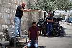 A Palestinian man uses a piece of cardboard to cover a man from the soaring heat as he pray outside the Lion's Gate a main entrance to the Al-Aqsa mosque compound in Jerusalem's Old City on July 24, 2017 as Palestinians protest against Israel's newly-installed security measures at the entrance to the al-Aqsa mosque compound. Photo by Amir Abed Rabbo