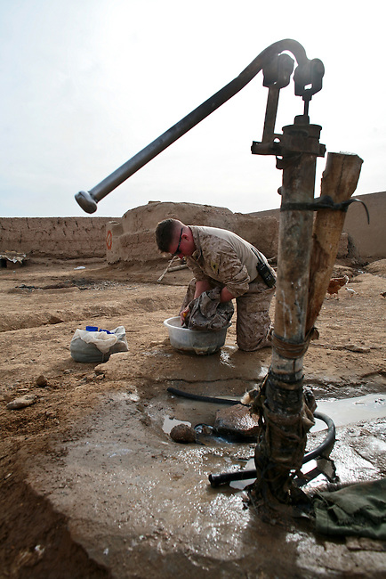 Cpl. Steven Atkins, 23, of Rochester Hills, Mich., washes a dirty uniform at Combat Outpost Coutu near Marjah, Afghanistan. Hand-pumped water is one of the few amenities at the compound, where the Marines of Company L, 3rd Battalion, 6th Marine Regiment have been living since 7,000 U.S. and Afghan troops seized the district last month. March 9, 2010. DREW BROWN/STARS AND STRIPES