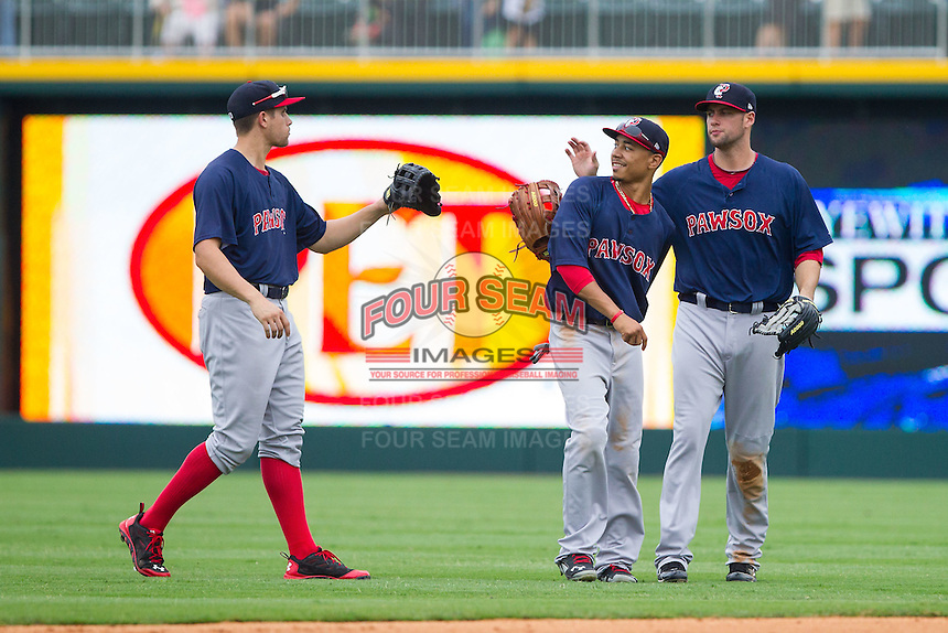 {L-R) Garin Cecchini (3), Mookie Betts (12), and Alex Hassan (21) congratulate each other after their win over the Charlotte Knights at BB&T Ballpark on August 10, 2014 in Charlotte, North Carolina.  The Red Sox defeated the Knights  6-4.  (Brian Westerholt/Four Seam Images)