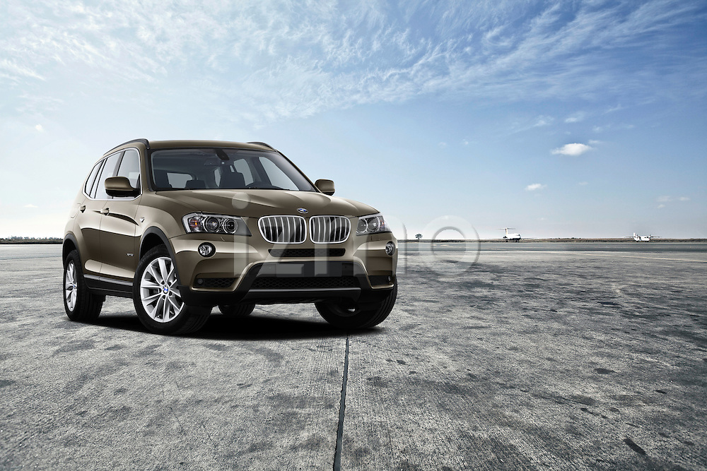 One bronze metalic 2011 BMW X3 XDrive35i SUV park outdoors on runway.