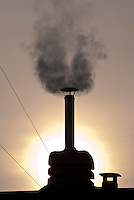 Milano, fumo da un comignolo su un tetto in periferia --- Milan, smoke from a chimney on a roof in the periphery
