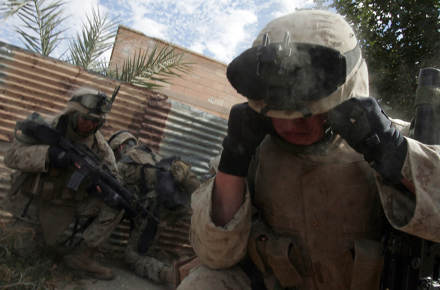 Members of Golf Co. 2nd Battalion 1st Marines plug their ears against the sound and shock wave of an explosive charge set to blow open a door as they clear house by house during Operation Steel Curtain, an operation to clear Husaybah (a city on the Iraq-Syrian border) of insurgents on Sun. Nov. 6, 2005. The operation has been labeled by the US military as largest since Fallujah involving more 2,500 US personnel and 1,000 Iraqis.