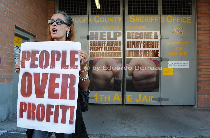"""Phoenix, Arizona. September 17, 2012 - A small crowd of demonstrators in Phoenix, Arizona gathered to mark one year since the beginning of the Occupy Movement that opposes Wall Street and large corporations that represent the one percent who control wealth in the United States. In this photograph, a woman holding a sign that reads """"People Over Profit,"""" protests outside the Fourth Avenue Maricopa County Jail -located in downtown Phoenix. The woman was part of the Occupy Phoenix group. Photo by Eduardo Barraza © 2012"""