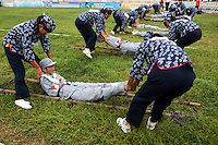 Female competitors dressed as revolutionary volunteers pick up 'wounded soldiers' from the 'battlefield' in the 'Rescue the Wounded Soldier' event of the Red Games. Held in Junan County, this sporting event is a nostalgic tribute to the communist era.