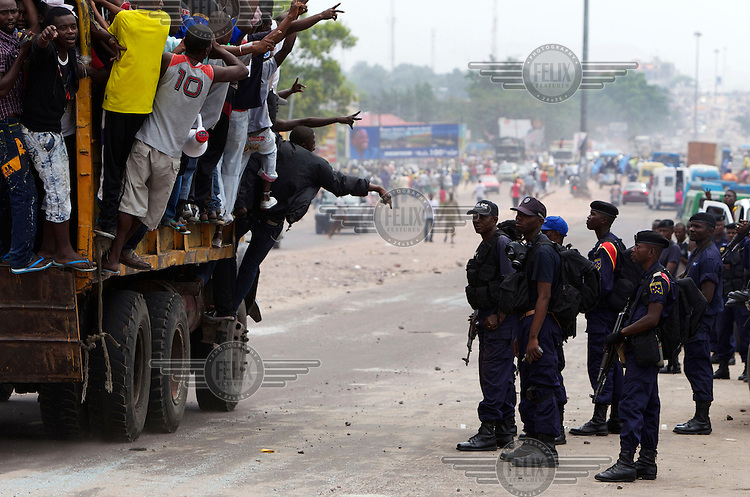 Union pour la Democratie et le Progres Social (UDPS) opposition party supporters pass police during violence leading up to the DRC's presidential and National Assembly elections.