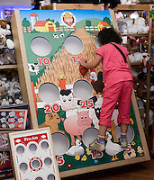 Quebec city, August 1, 2008 - Meriem Khalfoun climbs on a giant bean bag board on display at the Benjo toy store on St-Joseph street in Quebec city. Benjo is a 28,000-square-foot game and toy store filled with dolls, teddy bears, crafts, candy, model trains and cars, and more.