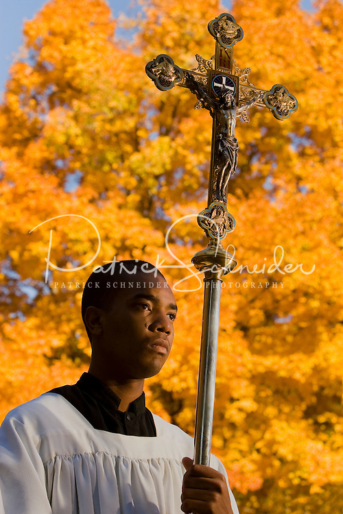 An altar boy holds a crucifix as he waits to process into a chapel on the campus of Belmont Abbey in Belmont, NC.
