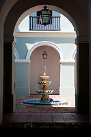 Small fountain in courtyard, framed by arched doorway in Old San Juan.