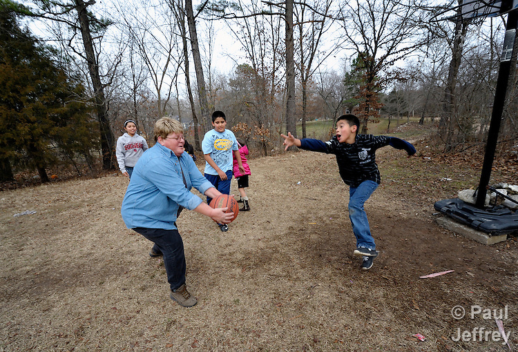 Debbie Humphrey, a United Methodist deaconess, is program director for the Cookson Hills Center, a ministry of The United Methodist Church in Cookson, Oklahoma. Humphrey coordinates work with children. Here she plays basketball with children in an isolated rural community.