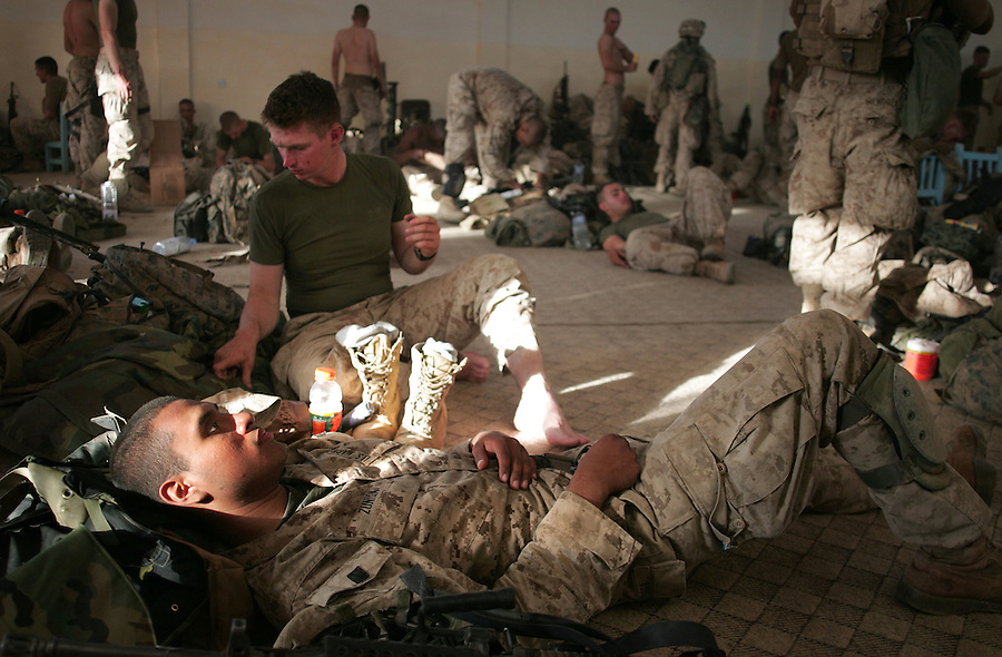 The Marines of Kilo Co. 3rd Battalion 1st Marine Regiment (3/1) eat, relax, and treat themselves for heat and aching muscles after a long day of searching for insurgents and weapons in the Al-Anbar Province city of Haditha on Thursday, Oct. 6, 2005 as the battalion continues with Operation River Gate.
