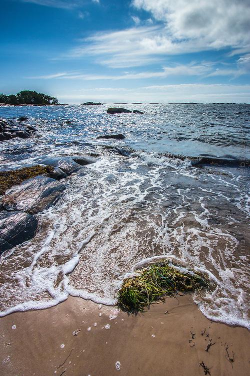 Våg från havet sköljer mot sandstrand på Sandhamn i  Stockholms skärgård