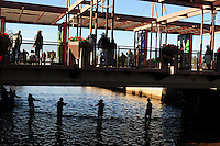 Scottsdale, Arizona (January 12, 2013) - As part of a seven-year plan to dry up all portions of its 131-mile canal system, Salt River Project (SRP), relocated the White Amur fish they used as an environmentally friendly and cost effective alternative to herbicides and heavy machinery for vegetation control. In this image, community residents stand on the Marshall Way Bridge in the city of Scottsdale to observe the process of herding fish by SRP workers. Photo by Eduardo Barraza © 2013