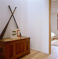 A pair of oars form part of an artwork on a wooden chest in the hall