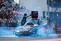 Oct 20, 2019; Ennis, TX, USA; Smoke comes from beneath the car of NHRA funny car driver Shawn Langdon as a crew member lifts his roof hatch following a burnout during the Fall Nationals at the Texas Motorplex. Mandatory Credit: Mark J. Rebilas-USA TODAY Sports