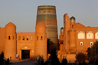General view of Ata-Davarza, built in 1842, demolished in 1920 and rebuilt in 1975, main gate of Ichan-Kala, Khiva, Uzbekistan, pictured on July 5, 2010 in the summer late afternoon light. In the background stands the blue-tiled Kalta Minar, 1855, also called Guyok Minar with the Muhammad Aminkhan Madrasah on its right.